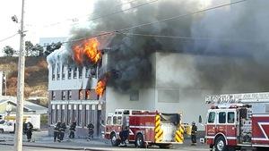 Des pompiers devant un bâtiment en feu