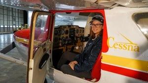 Sara Striker est assise sur le siège du pilote d'un petit avion. Elle regarde à travers la portière ouverte de l'avion qui se trouve dans un hangar.