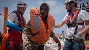 Un jeune homme africain portant une veste de sauvetage est flanqué de deux hommes travaillant pour SOS Méditerranée sur le pont de l'Aquarius.