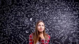 Une adolescente réfléchit devant un tableau noir où il y a des calculs mathématiques