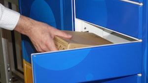 Une main qui sort un colis d'un casier bleu