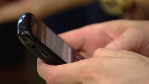 Une personne écrit un message sur un téléphone cellulaire
