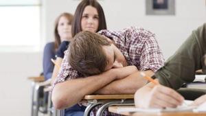 Un étudiant fait une sieste, appuyé sur ses bras, dans une classe remplie d'élèves attentifs