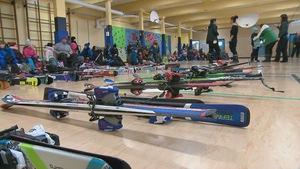 Des skis sont alignés dans le gymnase de l'école Saint-Jean-Baptiste
