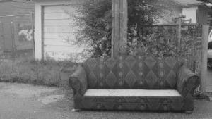 Photo en noir et blanc d'un sofa placé à la rue.