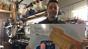 Marc Croussette pose avec un panneau informatif sur le dispositif