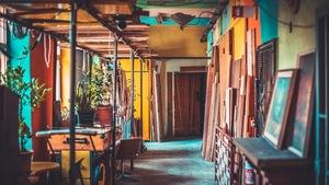 Un local coloré pour artistes avec des tables, des tableaux et des plantes.