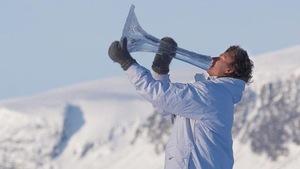 Un homme chaudement habillé souffle dans une énorme trompette transparente. L'angelot des neiges se trouve dans quelque paysage montagneux.