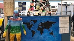 Trois œuvres d'art pris en photo au Pavillon secondaire des Quatre-Vents. En avant-plan, une figure en papier mâché aux couleurs dorées, vertes, bleues et rouges. Juste en arrière, une carte du monde avec des points rouges avec une silhouette en carton enrobée de drapeaux de pays et de photos divers.