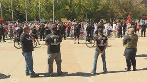 4 hommes debout devant la police et les manifestants antifascistes