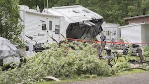 Une roulotte est couchée sur son flanc parmi les branches d'arbres cassées.