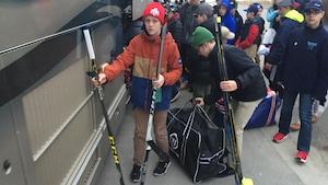 Des jeunes joueurs de hockey près de l'autobus avec leur sac.