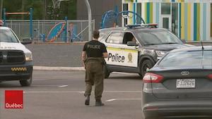 Un policier entouré de véhicules d'urgence dans la cour d'une école primaire.