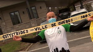 Simon Blouin tient un bandeau indiquant qu'il a complété le défi de la Ville de Québec à 100%.
