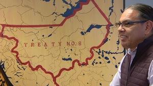 Le directeur général du centre, Daren Keewatin, apparaît à droite de l'image, souriant devant une carte montrant les limites du territoire accordé aux Premières Nations en vertu du Traité 8.