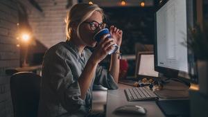 Une jeune femme boit un café en regardant un écran d'ordinateur assise à un bureau.
