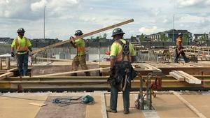 Des travailleurs de la construction déambulent sur un toit, un d'entre eux transportant une longue planche.
