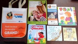 Des livres, des magazines et des dépliants sont placés sur une table à côté d'un sac disant «Petit lecteur deviendra grand».