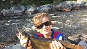 Un jeune garçon accroupi sur des roches au bord d'une rivière tient une truite mouchetée fraîchement pêchée.