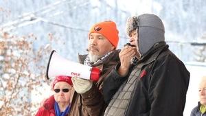 Des hommes qui sont à l'extérieur sont habillés en vêtements d'hiver et parlent devant un public.