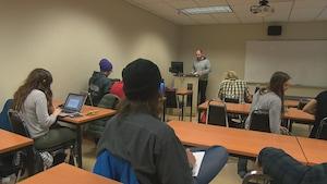Étudiants de dos dans une salle de classe devant un professeur.