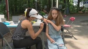 Une femme qui porte un masque chirurgical est en train d'injecter une dose de vaccin dans le bras d'une jeune fille. Toutes les deux sont assises, la scène se passe en extérieur.