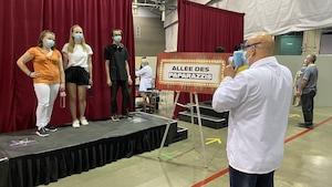 Des jeunes se font prendre en photo au centre de vaccination d'ExpoCité.