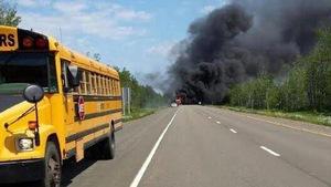 Un épais panache de fumée noire se dégage du véhicule en feu.
