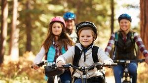 Une famille roule à vélo sur une piste boisée. Il y a deux adultes et deux enfants.