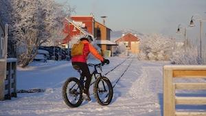 Une femme de dos sur un vélo en hiver, à Whitehorse, au Yukon