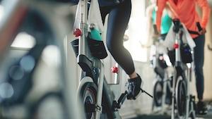 On voit des gens qui s'entraînent sur des vélos stationnaires. L'image est focalisée sur leurs jambes en action (on ne voit pas les visages).