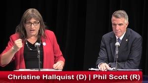 La candidate Christine Hallquist parle au micro, alors que Phil Scott l'écoute