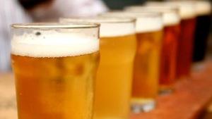 Des verres de bières alignées sur un comptoir.