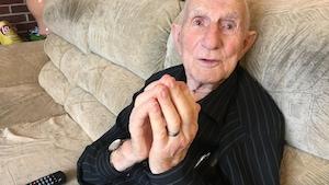 Un vieil homme assis sur un sofa.