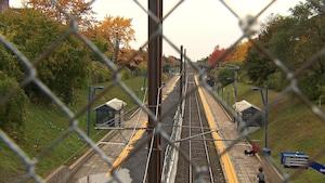 Le rail vu à travers le grillage d'une clôture.