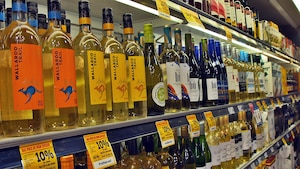 Des rangées de bouteilles de vin dans une épicerie