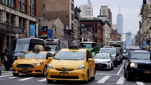 Rue bondée de Manhattan, taxis en avant-plan vus de face et voitures, édifices en arrière-plan.