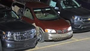 Un homme tente de voler un pneu d'un VUS stationné dans un concessionnaire automobile.