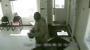 Un individu en train de commettre un vol dans une banque.