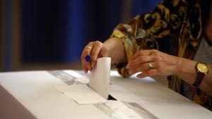 Les mains d'une personne qui met un ballot de vote dans une urne