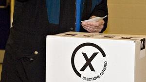 Photo d'un électeur en train de mettre son bulletin de vote dans la boîte de scrutin.