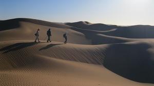 Trois personnes marchant dans le désert du Sahara au Maroc