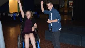 Une élève dans un fauteuil roulant, dansant avec un élève debout lors du mini-bal des finissants.