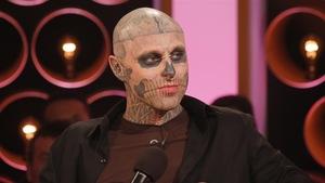 Un jeune homme au visage tatoué d'une tête de mort regarde l'animatrice d'une émission sur le plateau de tournage.