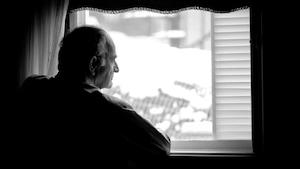 Un homme regarde par la fenêtre