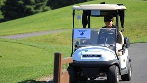 Raymonde Michaud au volant d'une voiture de golf.
