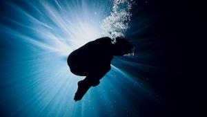 Jennifer Abel se tient sous l'eau, recroquevillée.