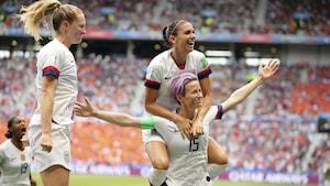 Alex Morgan saute sur les épaules de Megan Rapinoe (à droite) pour célébrer le but de cette dernière en finale de la Coupe du monde féminine entre les Américaines et les Néerlandaises.