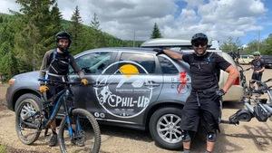 Philippe Dion pose devant une voiture aux couleurs de son entreprise en compagnie d'un client et de son vélo de montagne.