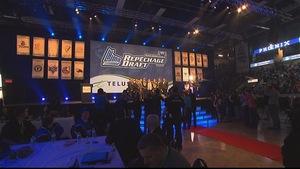Une séance de repêchage de la LHJMQ au Palais des sports Léopold-Drolet de Sherbrooke. On y voit une équipe sur la scène devant une salle comble.